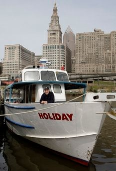 Wayne Bratton poses on his tour boat, 'Holiday' docked on the Cuyahoga River in Cleveland Tuesday, April 20, 2010.… Read more » (AP Photo/Mark Duncan)