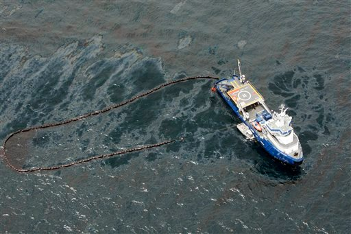 A boat with an oil boom tries to contain oil spilled from the explosion and collapse of the Deepwater Horizon oil rig, approximately seven miles from where the rig sunk, on Friday, April 23, 2010. (AP Photo/Gerald Herbert)
