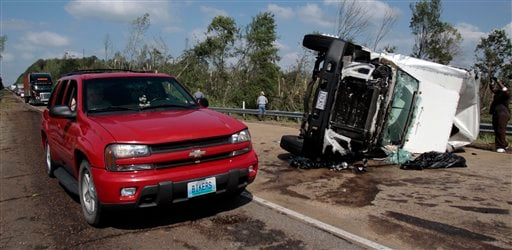 A motorist drives past an overturned truck which was among several vehicles damaged when a tornado crossed Interstate Highway 55 south of Durant, Miss., Saturday, April 24, 2010. (AP Photo/Rogelio V. Solis)