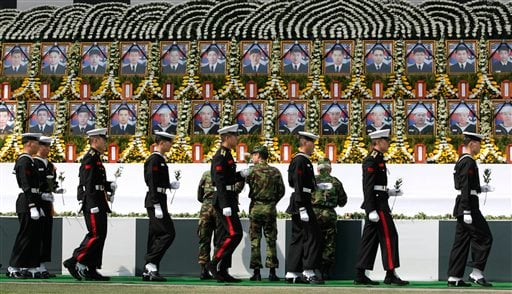 South Korean honor guard soldiers walk by the portraits of the deceased sailors from the sunken South Korean naval ship Cheonan during a memorial service at Seoul City Hall Plaza in South Korea, Sunday, April 25, 2010. (AP Photo/Ahn Young-joon)