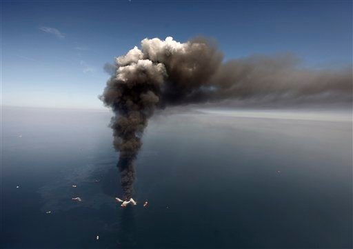 This Wednesday, April 21, 2010 aerial photo shows oil in the Gulf of Mexico, more than 50 miles southeast of Venice on Louisiana's tip, as the Deepwater Horizon oil rig burns.  (AP Photo/Gerald Herbert)