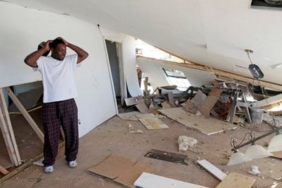 Dennis Richardson of Yazoo City, Miss., shakes his head after inspecting the collapsed ceiling from tornado damage to the house.
