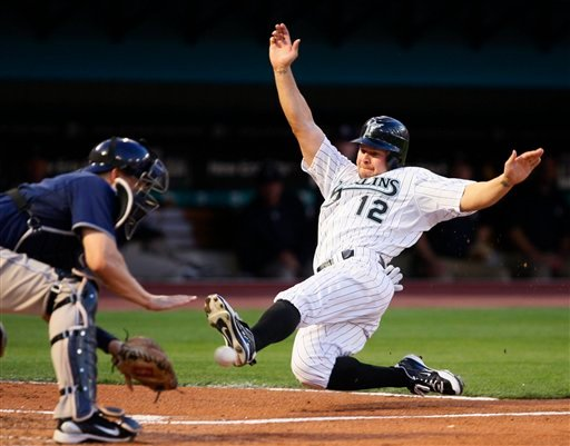 Florida Marlins' Cody Ross (12) slides safely into home as San Diego Padres catcher Nick Hundley attempts the catch on a single by Josh Johnson (not shown) during the second inning Monday, April 26, 2010 in Miami. (AP Photo/Wilfredo Lee)