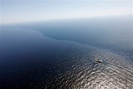 In this aerial photo taken over the Gulf of Mexico, a boat and crew work in oil which leaked from a pipeline at the Deepwater Horizon oil rig off the coast of Louisiana, Monday, April 26, 2010. (AP Photo/Gerald Herbert)