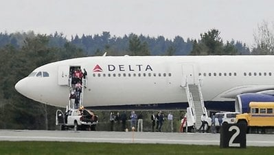People walk out of this Delta Air Lines Flight from Paris to Atlanta which was diverted to Bangor International Airport in Bangor, Maine Tuesday April 27, 2010.