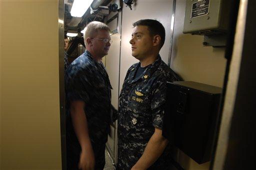 U.S. Navy Lt. j.g. Jeremy Huls, left, passes executive officer Lt. Cmdr. Daniel Lombardo, right, in a narrow passage way onboard the submarine U.S.S Alaska.