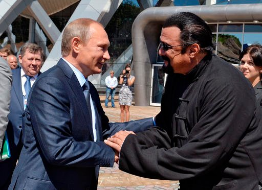In this Sept. 4, 2015 file photo, Russian President Vladimir Putin, left, and U.S. actor Steven Seagal shake hands after visiting an oceanarium built on Russky Island, in the Russian Far Eastern port of Vladivostok.