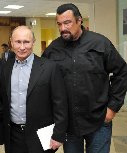 In this file photo taken on Wednesday, March 13, 2013, Russian President Vladimir Putin, left, and U.S. movie actor Steven Seagal visit a new sports arena in Moscow, Russia.