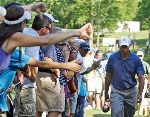 A woman, left, gives a thumbs down as Tiger Woods walks from the 15th hole during the second round of the Quail Hollow Championship golf tournament at Quail Hollow Club in Charlotte, N.C., Friday, April 30, 2010. (AP Photo/Chuck Burton)