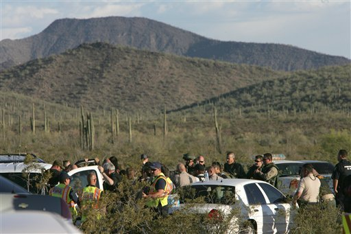 Law enforcement officers from different agencies gather to coordinate the search for a suspect that shot a Pinal County Sheriff's deputy Friday April 30, 2010 in the desert southwest of Stanfield, Ariz. (AP photo/Casa Grande Dispatch, Oscar Perez)
