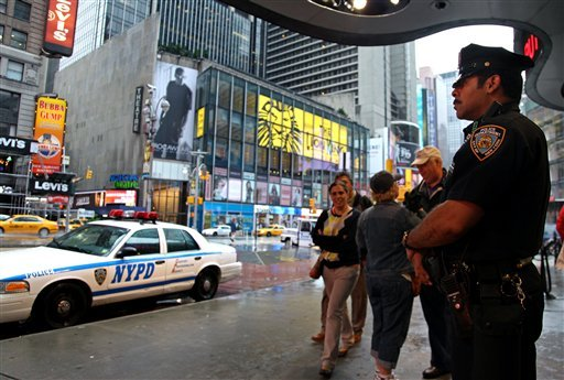 A New York City police officer stands watch on Times Square in New York, Monday, May 3, 2010, as pedestrians pass by. Activity appeared normal in the wake of a car bomb incident over the weekend. (AP Photo/Craig Ruttle)
