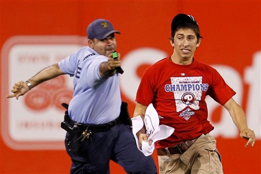 A law enforcement officer chases down a fan that ran onto the field before the eighth inning of a baseball game between the Philadelphia Phillies and the St. Louis Cardinals, Monday, May 3, 2010. (AP Photo/Matt Slocum)