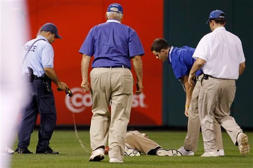 A law enforcement officer and stadium personnel check on fan that was chased down after running onto the field before the eighth inning of a baseball game between the Philadelphia Phillies and the St. Louis Cardinals. (AP Photo/Matt Slocum)