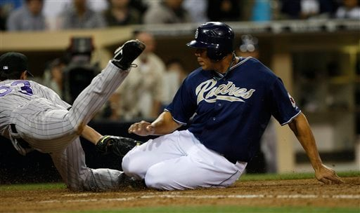 San Diego Padres' Kyle Blanks is out at home as Colorado Rockies relief pitcher Randy Flores reaches back to make the tag after a wild pitch in the sixth inning of a baseball game Tuesday May 4, 2010 in San Diego.