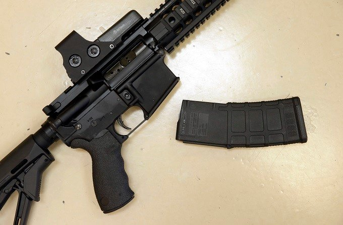 This Oct. 3, 2013 file photo shows a custom-made semi-automatic hunting rifle with a high-capacity detachable magazine is displayed at a gun store in Rockin, Calif. California voters are considering expanding some of the nation's toughest gun control meas