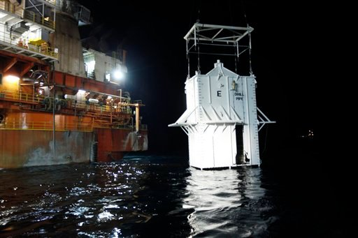 The containment vessel is lowered into the Gulf of Mexico at the site of the Deepwater Horizon rig collapse, Thursday, May 6, 2010. (AP Photo/Gerald Herbert)