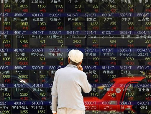 A man looks at an electric stock board in downtown Tokyo, Monday, April 26, 2010. (AP Photo/Shizuo Kambayashi)