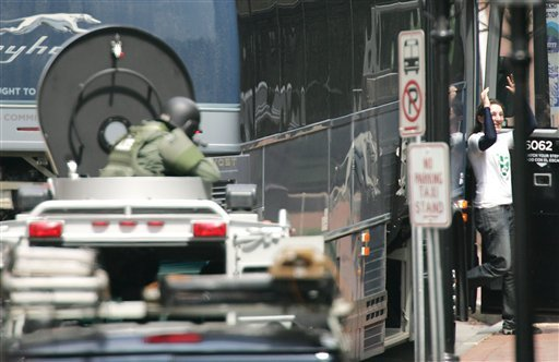 A hostage, right, is released during a bomb threat aboard a bus which cleared much of downtown Portsmouth, N.H., Thursday, May 6, 2010. (AP Photo/Jim Cole)
