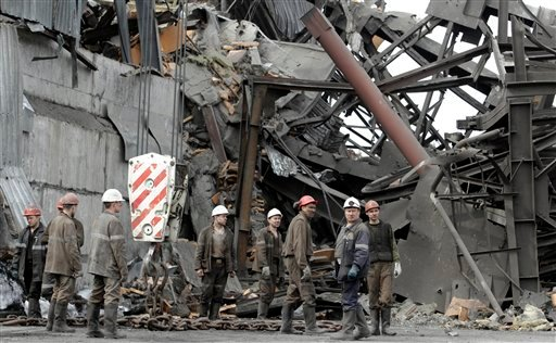 Emergency workers gather near the destroyed ventilation unit at the Raspadskaya mine, hit by explosions, in the city of Mezhdurechensk in the west Siberian region of Kemerovo, Russia, Monday, May 10, 2010. (AP Photo/Sergey Ponomarev)