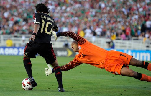 In this June 25, 2011, file photo, Mexico's Giovani Dos Santos, left, moves the ball as U.S. goalkeeper Tim Howard defends during the second half of the CONCACAF Gold Cup soccer final in Pasadena, Calif.