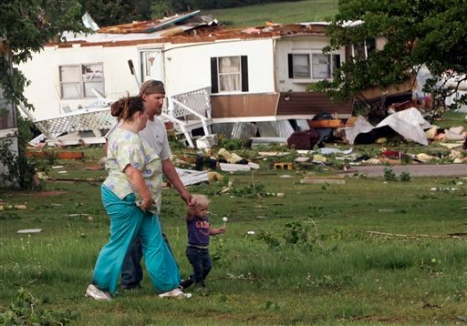 Residents Ryshele, left, and Ivanhoe Coleman, center, walk with their daughter Rikki, right, through what is left of Prairie Creek Village, a mobile home community in Slaughterville, Okla., after a tornado struck the area Monday, May 10, 2010. (AP Photo)