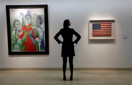 In this file photo of Feb. 5, 2010, an auction house worker poses for photographers between a 1961 Pablo Picasso painting, left, and a painting entitled 'Flag,' made between 1960-1966 by Jasper Johns, in central London.
