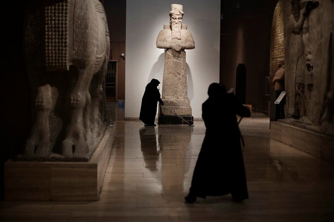 In this Sunday, March 13, 2016 file photo, Iraqi workers mop the floor at the Assyrian Hall of the Iraq National Museum Baghdad. Assyria was a civilization located near the modern-day city of Mosul, now held by the Islamic State group, who published video