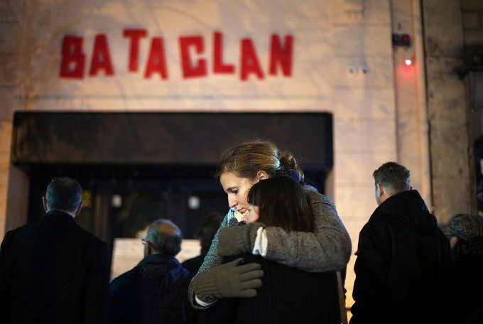 Women hug, in front of the Bataclan concert hall in Paris, Sunday, Nov. 13, 2016. France marked the anniversary of Islamic extremists' coordinated attacks on Paris with a somber silence on Sunday that was broken only by voices reciting the names of the 13