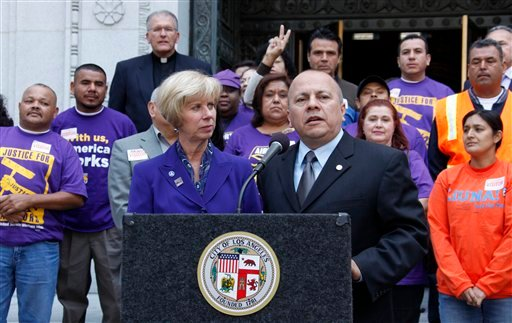 Joined by supporters, Los Angeles city council members Janice Hahn and Ed Reyes talk with reporters.