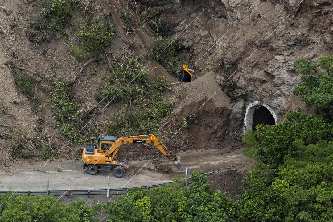 An excavator clears a landslide on a section of state highway 1 near Kaikoura, New Zealand, Monday, Nov. 14, 2016 after a powerful earthquake. (David Alexander/SNPA via AP)