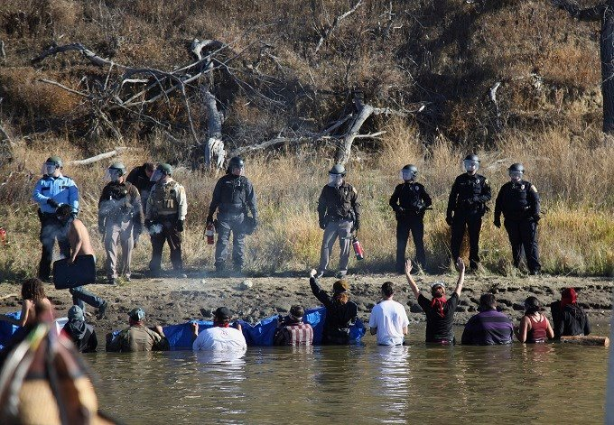In this Nov. 2, 2016 file photo, protesters demonstrating against the expansion of the Dakota Access Pipeline wade in cold creek waters confronting local police as remnants of pepper spray waft over the crowd near Cannon Ball, N.D. The U.S. Army Corps of