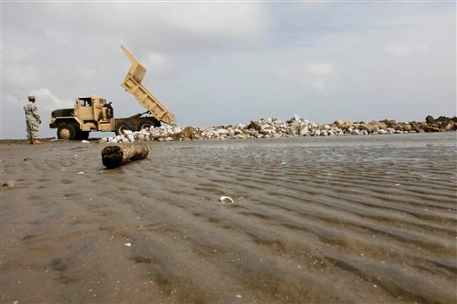 Members of the Louisiana National Guard build a levee to protect inland waterways fron the Deepwater Horizon oil spill on Elmer's Island in Grand Isle, La., Friday, May 14, 2010. (AP Photo/Gerald Herbert)