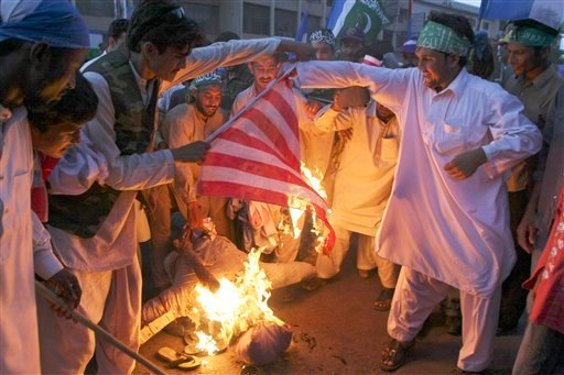 Supporters of a religious group Jamaat-e-Islami burn the effigy of U.S. President Barack Obama and a U.S. flag during a rally against alleged U.S. interference in Pakistani affairs, in Karachi, Pakistan. (AP Photo/Fareed Khan)