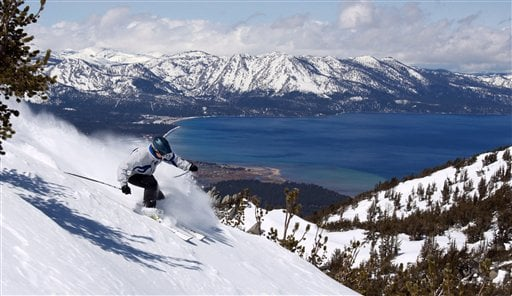 With Lake Tahoe as a backdrop, a skier kicks up some powder at Heavenly Ski Resort, Wednesday, April 14, 2010 in South Lake Tahoe, Calif. (AP Photo/Dino Vournas)