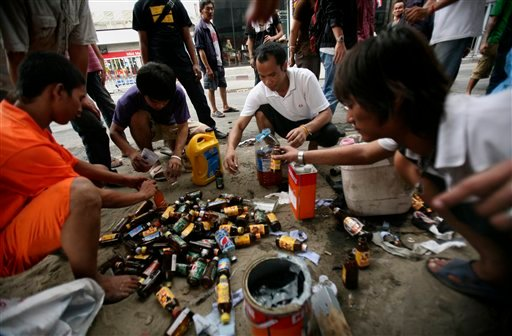 Anti-government protesters make petrol bombs in front of a stand off with Thai military, Sunday, May 16, 2010 in Bangkok, Thailand. (AP Photo/Wally Santana)
