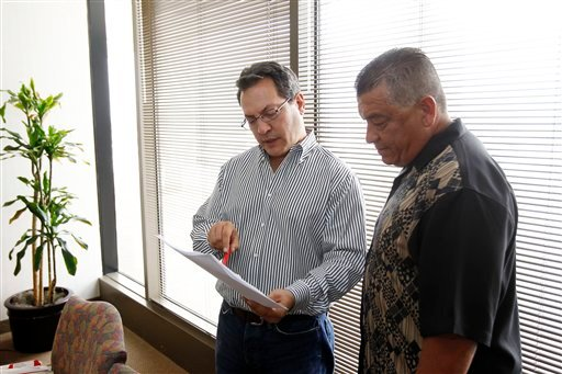 Phoenix police officer David Salgado, right, goes over his case with his lawyer Stephen Montoya in Phoenix on Monday, May 17, 2010. Salgado, an opponent of the new immigration law in Arizona, has sued the city of Phoenix and the governor over the measure.