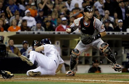 San Francisco Giants catcher Eli Whiteside looks to throw to first after forcing San Diego Padres' Nick Hundley at home during the fifth inning of a baseball game Tuesday, May 18, 2010, in San Diego. (AP Photo/Lenny Ignelzi)