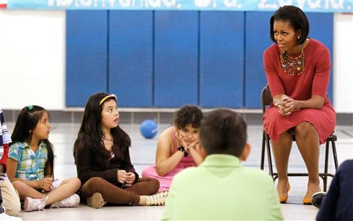"First lady Michelle Obama, right, talks with students, including the second-grader, far left, who told Obama during the first lady's visit to her gym class that her mother said President Obama was ""taking everybody away that doesn't have papers."""