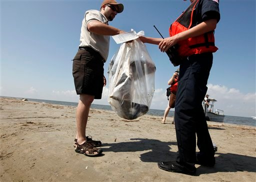 U.S. Fish and Wildlife officer Raul Sanchez hands off a dead oil-covered pelican to an unidentified Coast Guard personnel after bagging and tagging it as evidence on North Breton Island, La., Thursday, May 20, 2010. (AP Photo/Gerald Herbert)