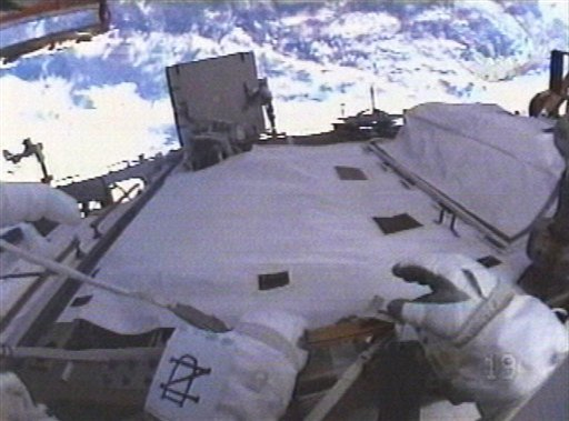 In an image made from NASA TV, astronaut Michael Good participates in a spacewalk wearing a Notre Dame logo on the left arm of his space suit on Friday, May 21, 2010.