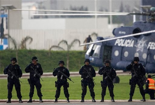 In this July 3, 2008 file photo Mexican Federal Police stand at attention in the rain after demonstrating an operation to the press.