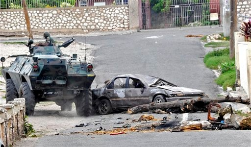 In this photo taken Wednesday, May 19, 2010 a Jamaica Defense Force armored vehicle make its way into a barricaded street in Hannah Town, West Kingston. (AP Photo/The Jamaica Gleaner, Norman Grindley)
