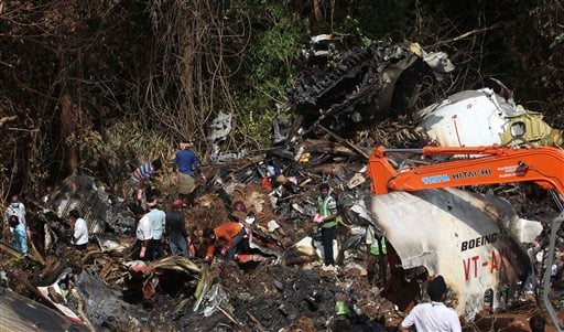 An earth remover cleans the site of the crash of an Air India Boeing 737-800 plane in Mangalore, in the southern Indian state of Karnataka, Monday, May 24, 2010.  (AP Photo/Rafiq Maqbool)