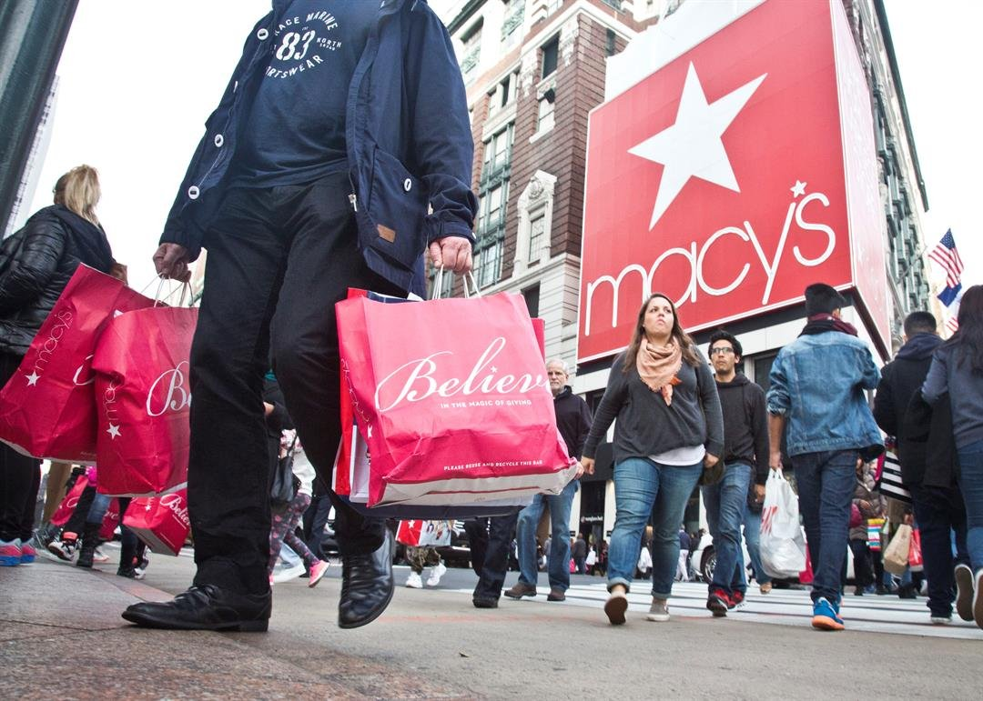 Friday, Nov. 27, 2015, file photo, shoppers carry bags as they cross a pedestrian walkway near Macy's in Herald Square, in New York. (AP Photo/Bebeto Matthews, File)