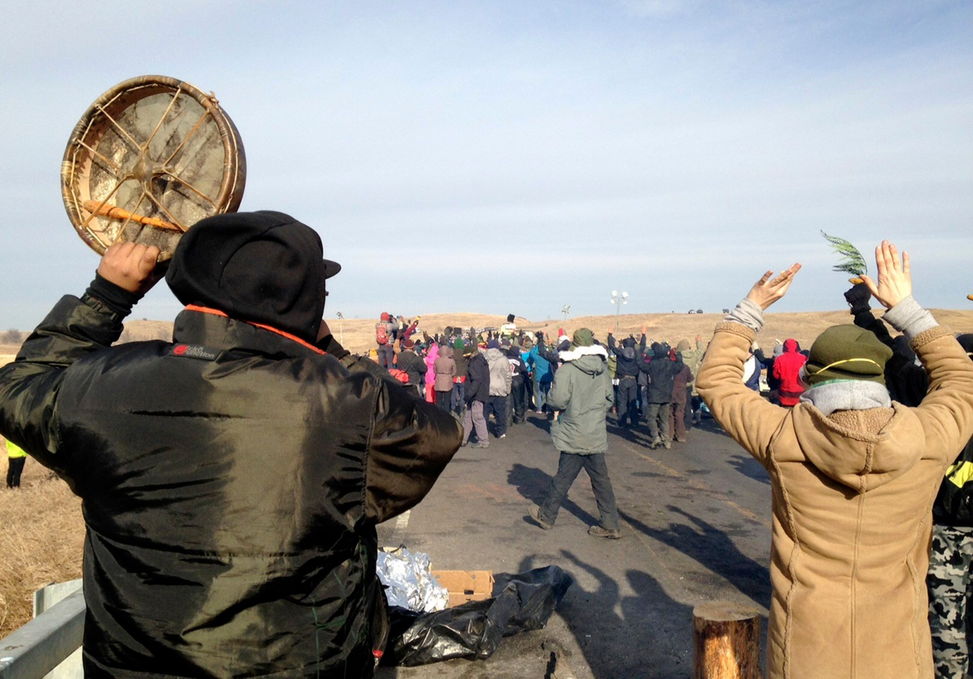 Protesters against the Dakota Access oil pipeline congregate Monday, Nov. 21, 2016, near Cannon Ball, N.D., on a long-closed bridge on a state highway near their camp in southern North Dakota.