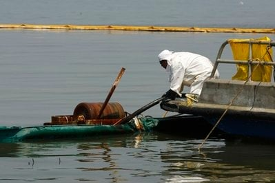 A contractor operates an oil skimmer near a marsh impacted from the Deepwater Horizon oil spill in Pass a Loutre, Monday, May 24, 2010.