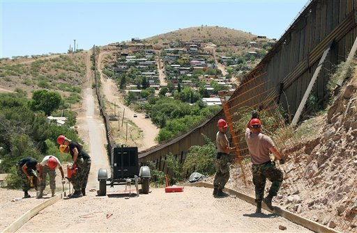 In this June 20, 2008 file photo, members of the 200th Red Horse Air National Guard Civil Engineering Squadron from Camp Perry in Ohio work on building a road at the border in Nogales, Ariz.