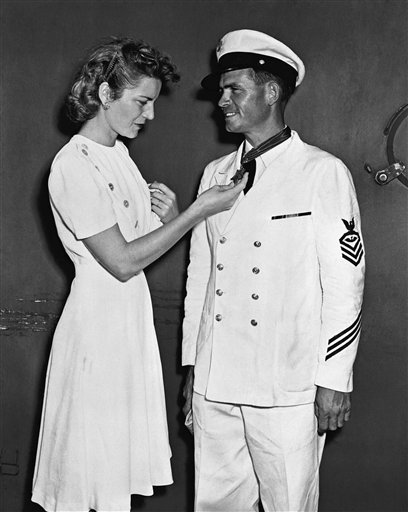 In this Sept. 28, 1942 photo provided by the U.S. Navy, Chief Ordnanceman John W. Finn is congratulated by his wife Alice at Pearl Harbor, Hawaii, after he was awarded the Congressional Medal of Honor.
