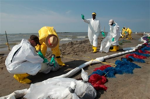 Workers clean up oil residue along the beach in Port Fourchon, La., Saturday, May 29, 2010. (AP Photo/Jae C. Hong)