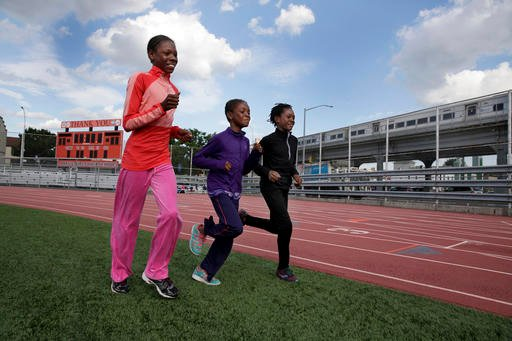 In this July 11, 2016 photo, Tai Sheppard, 11, Brooke Sheppard, 8, and Rainn Sheppard, 10, left to right, run warm-up laps at Boys and Girls High School, in the Brooklyn borough of New York.